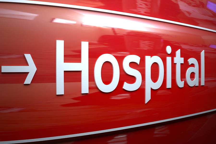 White Hospital sign on the shiny remarkable red wall.