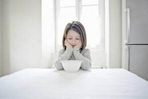 Girl examining empty bowl at table