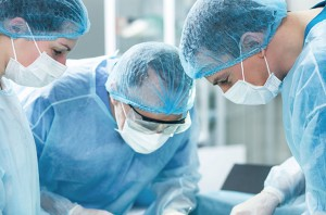 Professional surgical team is operating on a patient. The men are looking down with concentration. The female assistant is standing and helping them